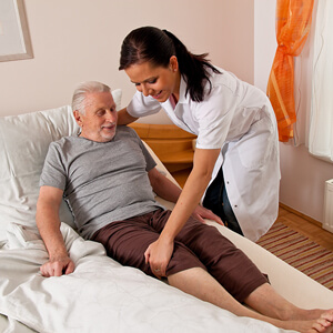 Nurse helping man sit up in bed